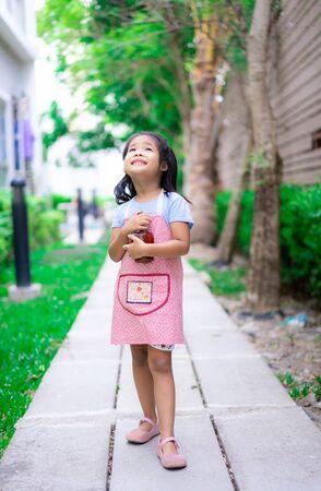 Portrait of little girl in apron with mortar in the garden Reklamní fotografie