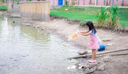A little girl feeding fish at the pond in public park