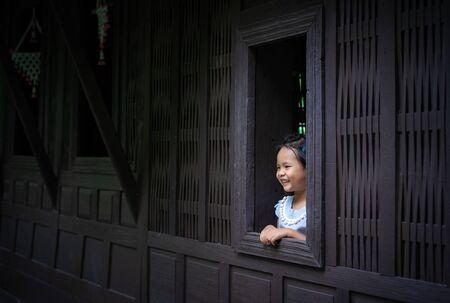 happy little asian girl standing by the window Banco de Imagens
