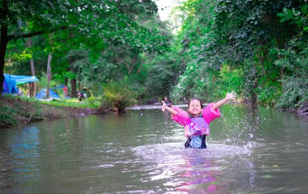 little asian girl wearing inflatable sleeves playing in nature water while camping on holiday