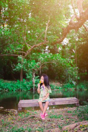 Little girl in green dress sitting on a swing in the park Stockfoto