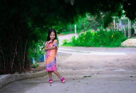 Portrait of happy asian little girl in dress standing on footpath in the park