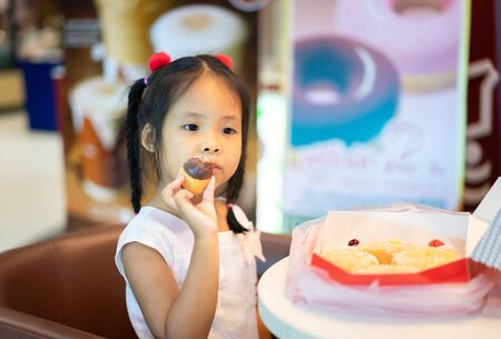 Little asian girl sitting on the chair with holding and eating donuts