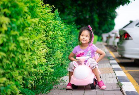 Asian little girl enjoys playing car on footpath