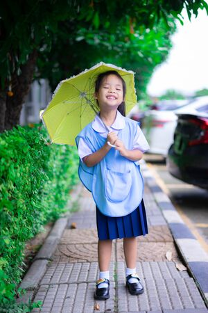 little girl in Thai school uniform with yellow umbrella in raining day