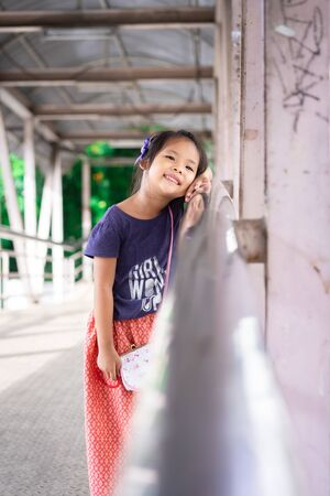 portrait of asian little girl on the bridge in the park