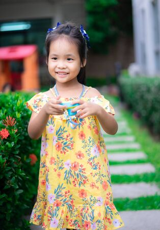 Portrait of cute little asian girl have fun with toy camera in the park