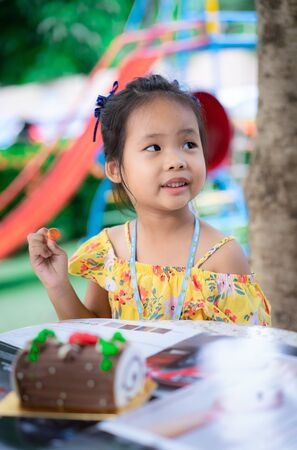 Portrait of little asian girl in yellow dress eating happy birthday cake outdoor Stockfoto