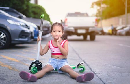 Cute little asian girl playing a scooter on the street Imagens