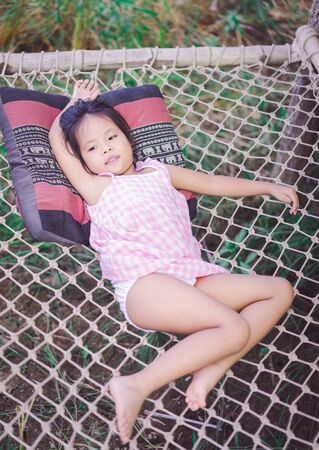 little asian girl is laying down on the net bench