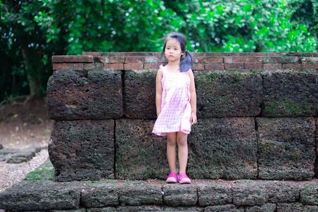 Little asian girl with dress standind on th rock of historic site in Thailand Stockfoto