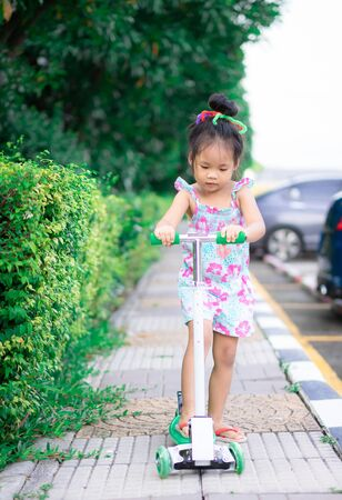 Cute little asian girl learning to ride a scooter on footpath