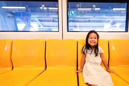 Asian little girl enjoy and fun in bogey of sky train or electric train for travel or transport in city on holiday