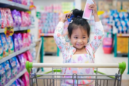little girl sitting in the cart between shopping with credit card