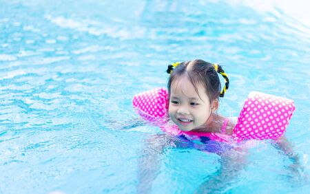 little asian girl wearing inflatable sleeves swimming in the pool Stockfoto