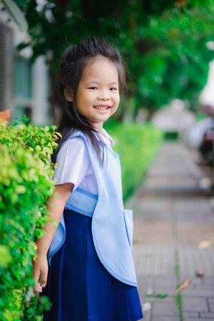 Portrait of happy little girl in Thai school uniform standing in the park, ready back to school Stockfoto