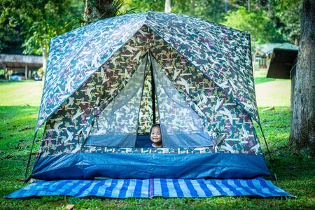little girl sitting in tent while going camping.The concept of outdoor activities and adventures in nature.