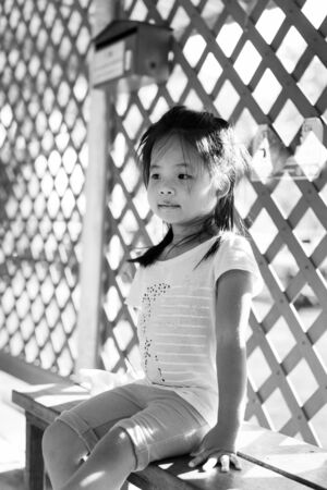little girl sitting on a bench in train station