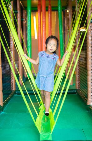 Asian little girl enjoys playing in a children playground Stock Photo