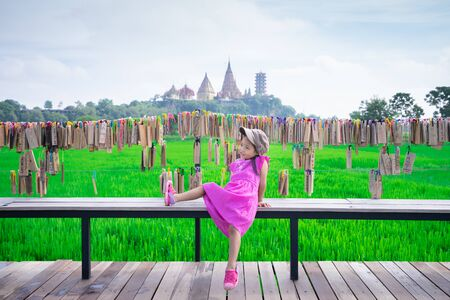 little girl wear hat sitting on a bench with temple background Stockfoto