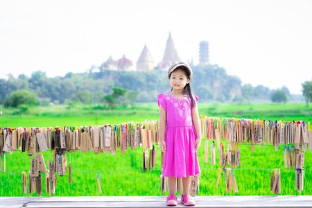 little girl wear hat standing on a bench with temple background