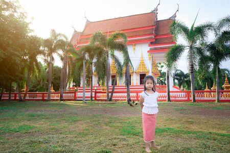 happy asian little girl in Thai period dress standing in the temple Standard-Bild