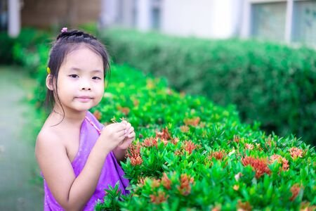 happy asian little girl in Thai period dress holding red flowers in hand