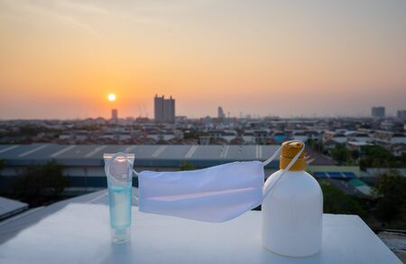 Mask face and alcohol gel for Coronavirus protection with city background