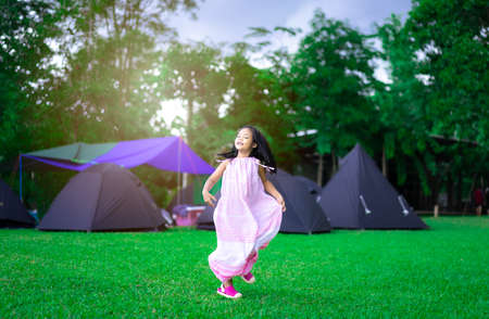 happy little asian girl in dress walking on the grass in front of tents while going camping with sunset 版權商用圖片