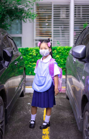 thai girl student wearing a mask against coronavirus and PM 2.5 air pollution before going to school 版權商用圖片