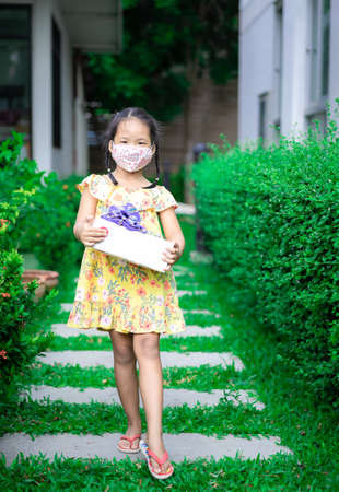 litte asian girl wearing mask in yellow dress holding present box in her birthday in the park
