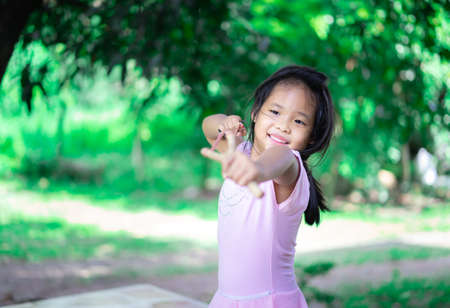 little asian girl shooting wooden slingshot against green tree background, active leisure for kids.