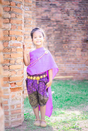 little asian girl in Thai period dress standing in ancient remains 版權商用圖片