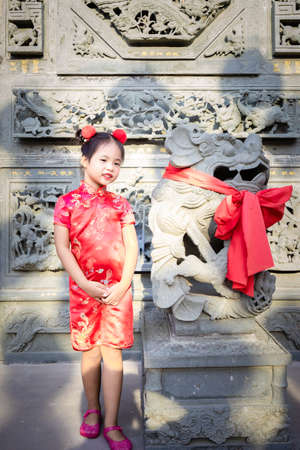 cute little asian girl in chinese traditional dress smiling and standing near statue.Happy chinese new year concept.