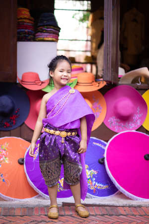 little asian girl in Thai period dress standing with colorful umbrella 版權商用圖片