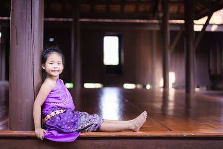 little asian girl in Thai period dress sitting in ancient house