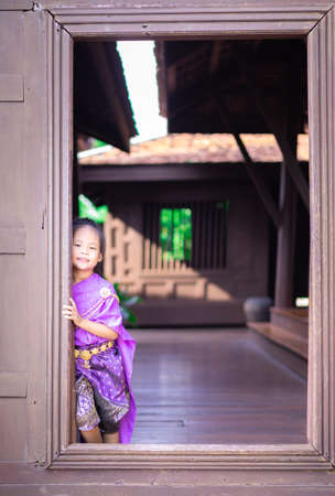 little asian girl in Thai period dress standing in ancient house 版權商用圖片