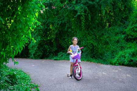 Cute little asian girl riding a bicycle to exercise in park, kids sport and active lifestyle