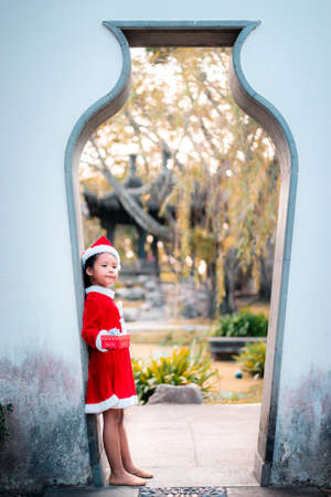 little asian girl in red Santa Claus costume with present box in the door