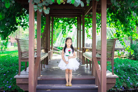cute little asian girl in white dress holding a red rose standing in the pavilion 版權商用圖片