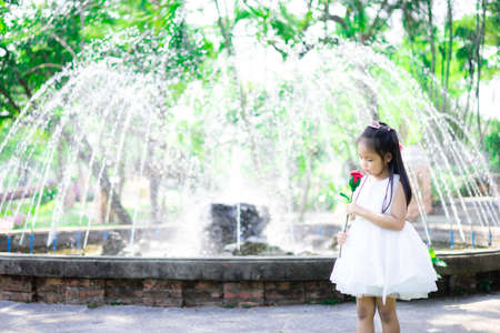 cute little asian girl in white dress holding a red rose in the park