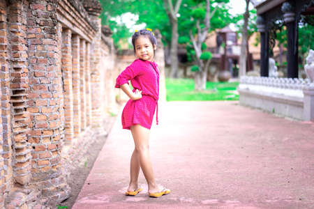Portrait of happy asian little girl in red dress standing in the park