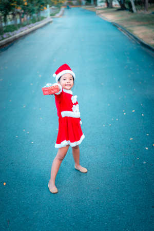 little asian girl in red Santa Claus costume with present box on the road