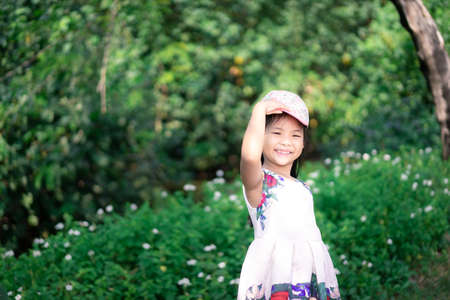 little asian girl in dress smiling while wearing cap in the park