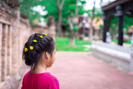 Side view of little asian girl in red dress with beautiful hair and yellow flower walking in the park 版權商用圖片
