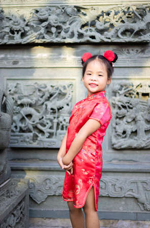 cute little asian girl in chinese traditional dress smiling and standing in the temple.Happy chinese new year concept. 版權商用圖片