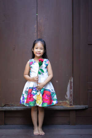 cute little asian girl in dress holding a red rose in home 版權商用圖片