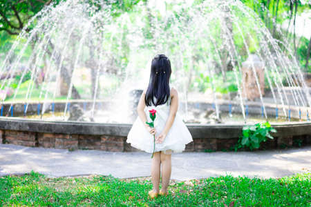 cute little asian girl in white dress stand back and holding a red rose in the park