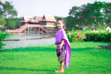 little asian girl in Thai period dress standing in the park