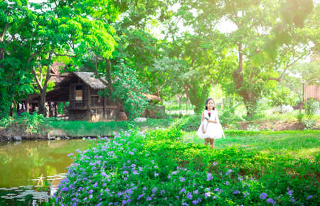 cute little asian girl in white dress standing and holding a red rose in the park